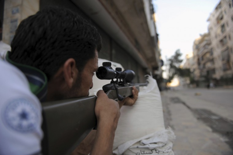 "A fighter from the Syrian opposition aims fire during clashes with forces loyal to President Bashar al-Assad, in the center of Syria's restive northern city of Aleppo on July 25, 2012. The Syrian army and rebels on July 25, sent reinforcements to Aleppo to join the intensifying battle for the country's second city, as UN chief Ban Ki-moon urged the world ""to stop the slaughter."" (Bulent Kilic/GettyImages)"