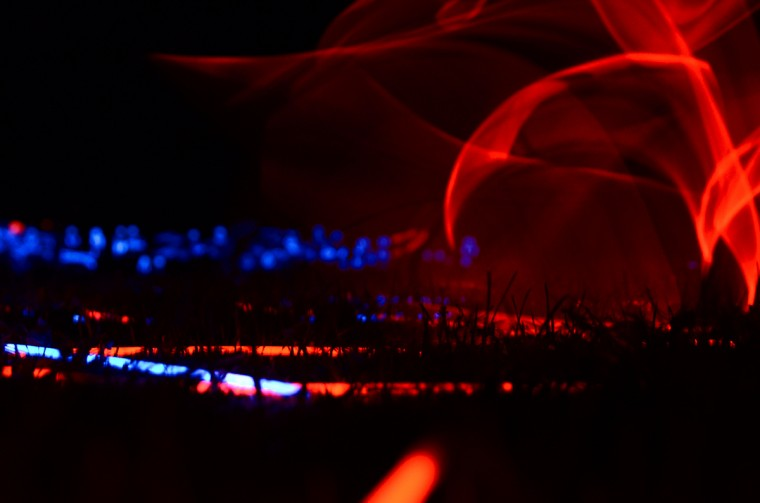 A red glow stick twirls near the ground before it settles in the grass by others. (Jon Sham)