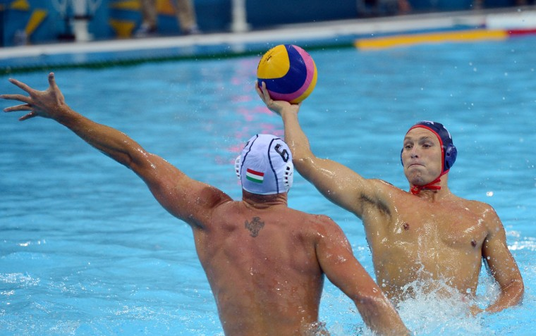 The USA's Adam Steinmetz, right, looks to pass against Hungary defender Norbert Hosnyanszky during the first half of a Group B match at the Water Polo Arena in Olympic Park during the 2012 Summer Olympic Games in London, England, Monday, August 6, 2012. Hungary defeated the USA, 11-6. (Chuck Myers/MCT)