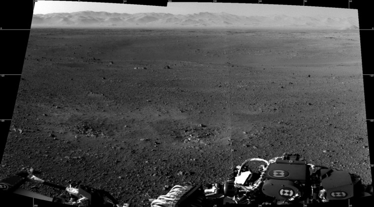"August 8, 2012: These are the first two full-resolution images of the Martian surface from the Navigation cameras on NASA's Curiosity rover, which are located on the rover's ""head"" or mast. The rim of Gale Crater can be seen in the distance beyond the pebbly ground. The topography of the rim is very mountainous due to erosion. The ground seen in the middle shows low-relief scarps and plains. The foreground shows two distinct zones of excavation likely carved out by blasts from the rover's descent stage thrusters. (NASA/MCT)"