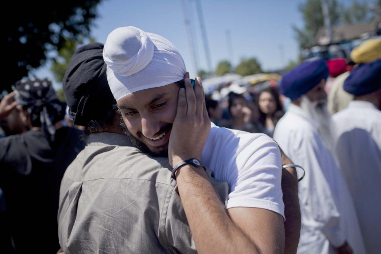 OAK CREEK - AUGUST 5: People embrace across the street after a shooting at the Sikh Temple in Oak Creek, Wisconsin, Sunday, August 5, 2012. (Chris Wilson/Milwaukee Journal Sentinel/MCT)
