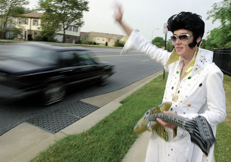 August 16, 2002: Stacey Aikman, the senior facility manager at Oak Crest Village retirement community, greets passers-by and Oak Crest Village employees on the 25th anniversary of Elvis Presley's death. (Steve Ruark/Patuxent Publishing)