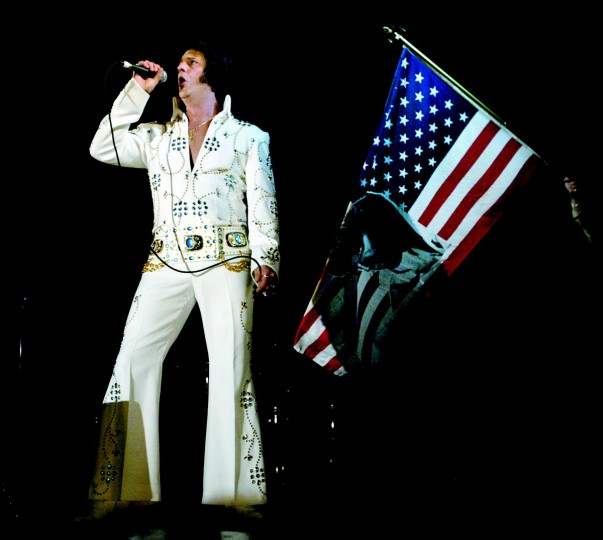 "December 3, 2004: Tommy El (also known as Tommy Barnes of Parkville) performs during the ""Night of 100 Elvises"" at the Lithuanian Hall in Baltimore. His wife is holding the Elvis American flag behind him. (Patuxent Publishing)"