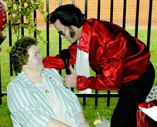 "August 10, 2004: Elvis impersonator Tom Connelly serenades Pat McCloskey during a surprise birthday party for her. ""Elvis"" also named McCloskey president of the Elvis Fan Club. (Patuxent Publishing)"