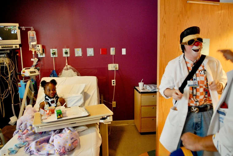"July 19, 2006: ""I must have one of the only jobs in the world where I can claim an Elvis Mask on my taxes."" Greg May, a Columbia-based variety entertainer, uses his newly bought prop to bring a smile to the face of six-year-old Taylor Young, from Ellicott City, one of the sick children he and his partner Bill Boots, from Arbutus, entertain at Johns Hopkins Hospital as part of a program put on through the Big Apple Circus Clown Care program. (Matt Roth/Patuxent Publishing)"
