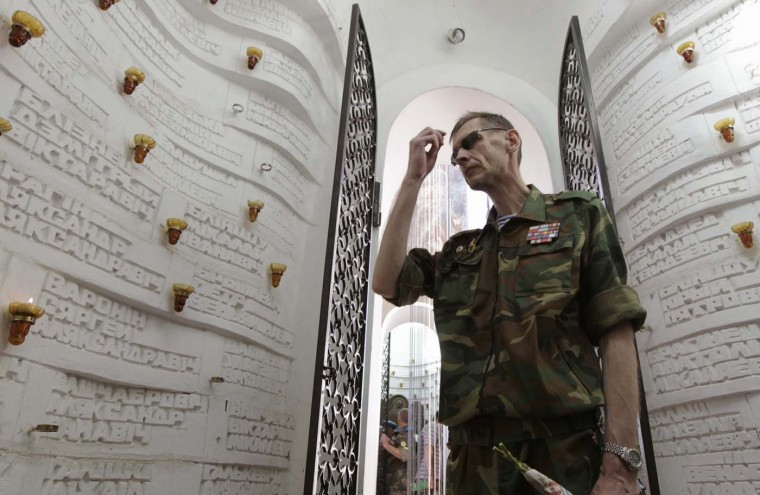 A former Belarusian paratrooper makes the sign of the cross inside a monument commemorating victims of the war in Afghanistan, which involved Soviet airborne troops during the 1980s, on Paratroopers Day in Minsk, August 2, 2012. The holiday for the airborne troops is celebrated in most of the post-Soviet countries. (Vasily Fedosenko/Reuters)