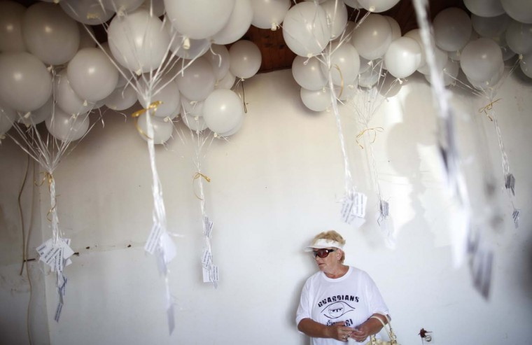 A visitor stands next to balloons in a building where inmates were tortured, during the 20th anniversary of the closure of the Omarska detention camp in Omarska, August 6, 2012. (Dado Ruvic/Reuters)