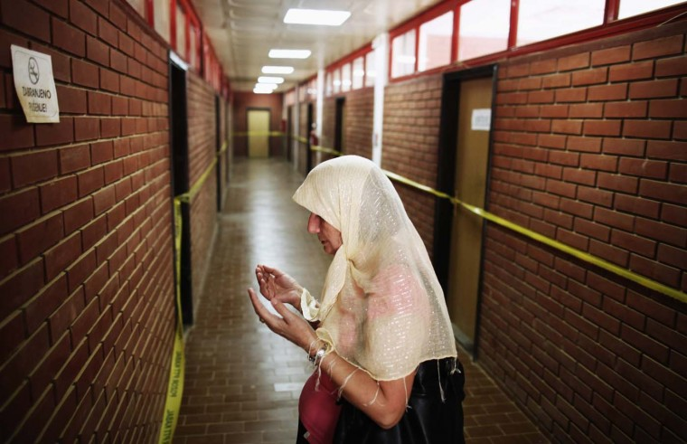 A Bosnian Muslim woman prays along a corridor with rooms where inmates were tortured, during the 20th anniversary of the closure of the Omarska detention camp in Omarska, August 6, 2012. Hundreds of former inmates released balloons with names of missing persons into the air during a ceremony marking its closure, commemorating around 800 people who died in the camp which housed approximately 5,000 people during the 1992 Bosnian war. (Dado Ruvic/Reuters)