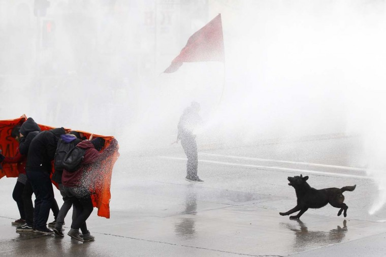 Student protesters are hit by a jet of water as they clash with riot policemen during a demonstration against the government to demand changes in the public state education system in Santiago, August 23, 2012. Chilean students have been protesting against what they say is profiteering in the state education system. (Ivan Alvarado/Reuters photo)