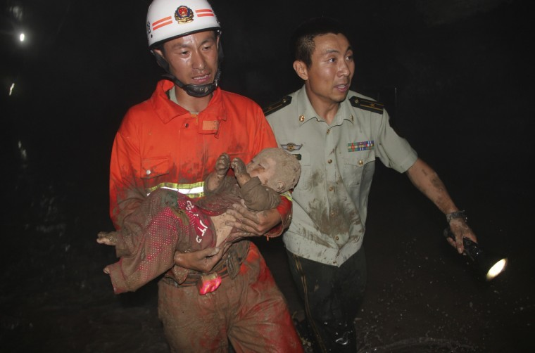 A firefighter (L) holds a 14-month-old baby who has been rescued from a pit caused by a road cave-in in Harbin, Heilongjiang province. According to local authorities, two people died from injuries sustained in the fall into a 10-meter-deep pit caused by a road cave-in in northeast China's Harbin city. (Xinhua News Agency/Reuters)