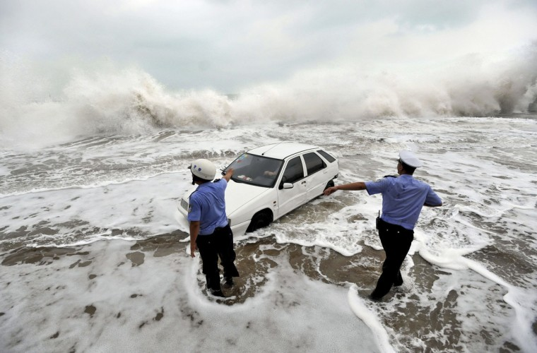 Policemen gesture to a driver stranded in a car on a flooded road as waves are whipped up by typhoon Bolaven in Qingdao, Shandong province. Gales and downpours brought by typhoon Bolaven swept through parts of northeast China from Tuesday evening to Wednesday, flooding cities and delaying flights, Xinhua News Agency reported. (Reuters)
