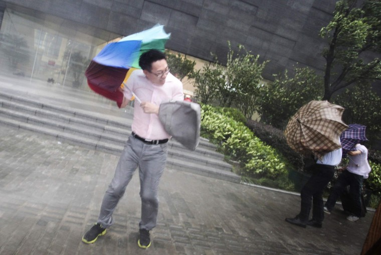 Pedestrians hold on to their umbrellas against strong winds and heavy rainfall on a street as Typhoon Haikui hits Shanghai. Typhoon Haikui struck China on Wednesday, packing winds of up to 110 km per hour (68 mph), prompting officials to evacuate nearly 2 million people and grounding hundreds of flights to and from Shanghai and other cities. (Reuters)