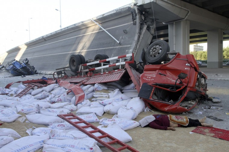 The body of a driver is seen next to overturned trucks and a collapsed bridge in Harbin, Heilongjiang province. The ramp of a multimillion-dollar bridge in northeast China collapsed early Friday morning, sending four trucks falling 30 meters to the ground, killing three people and injuring five. (Reuters)