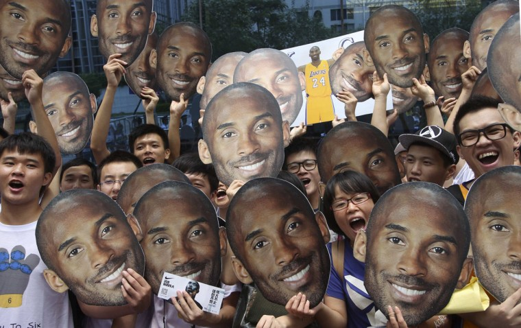 Fans hold posters of NBA basketball player Kobe Bryant as they wait for a promotional event in Guangzhou, Guangdong province in Chinca. (Alvin Chan/Reuters)