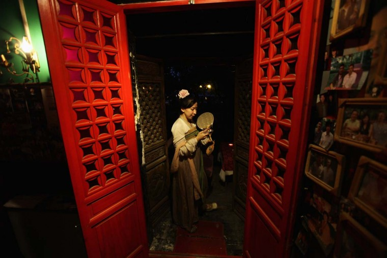 A woman dressed in a Han-dynasty costume checks her mobile phone ahead of a performance to celebrate the Qixi festival at an entrance of a tea house at Houhai area, in central Beijing. The Qixi festival, also known as the Double Seven Festival, is the Chinese version of Valentine's Day. (Jason Lee/Reuters photo)