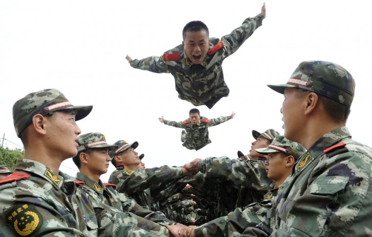 Paramilitary policemen jump up above their fellow policemen's arms as they take part in a psychological training in Tongling, Anhui province. (China Daily/Reuters)