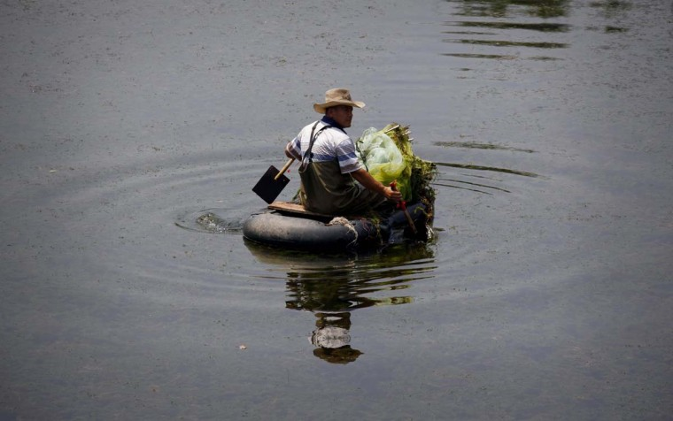 A fisherman collects nets as he paddles along a canal on an old inner-tube in Beijing August 31, 2012. (David Gray/Reuters photo)