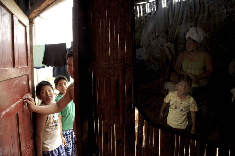 A woman and her children are reflected on a mirror at their home at Bastion neighborhood, in Guayaquil, August 4, 2012. Bastion is a neighborhood populated with thousands of squatters. (Guillermo Granja/Reuters)