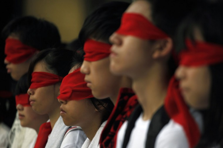 "Students cover their eyes with red ribbons as a symbolic gesture of refusing to be ""hoodwinked"" during a protest against a new Chinese national education course in Hong Kong. An expected 10,000 activists will head for the streets and march to the government headquarters on Saturday to demand the government scrap its plan to introduce the curriculum for students aged six years and older into schools on September 1, according to government radio. (Tyrone Siu/Reuters)"
