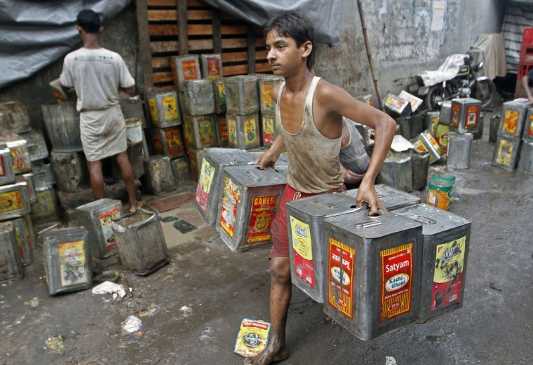Chotu, 14, carries recycled mustard oil tin containers from a roadside workshop in Kolkata. India's industrial output grew at a slower pace in June, hobbled by weak investment at home because of policy inaction and a drop in export orders from the United States and Europe, a Reuters polls showed on Tuesday. (Rupak De Chowdhuri/Reuters)