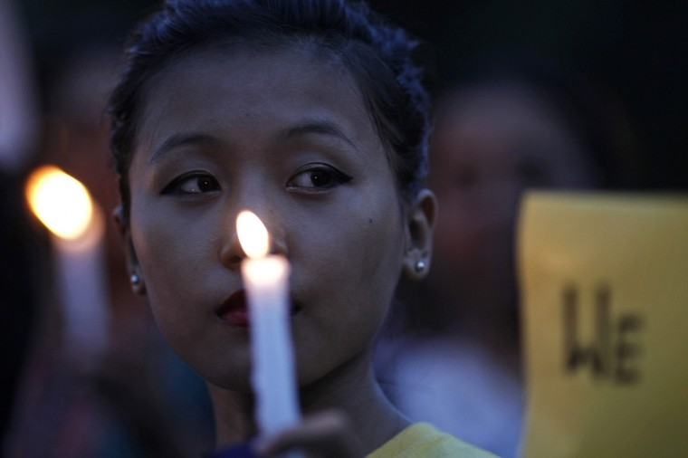 A woman holds a candle during a vigil to show solidarity with the people of Assam at a rally in front of the India Gate in New Delhi. Clashes between indigenous people in Assam and Muslim settlers from neighboring Bangladesh have killed nearly 80 people and displaced some 300,000 since July. (Adnan Abidi/Reuters)