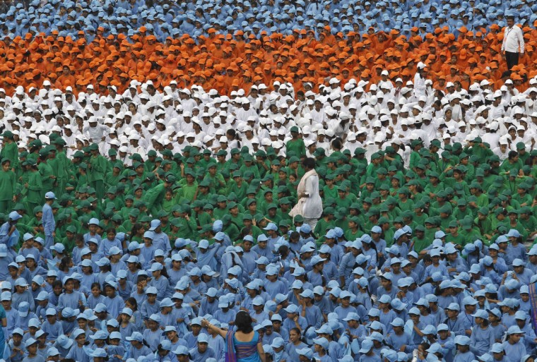 Schoolchildren take part in the Independence Day celebrations in front of the historic Red Fort, where Indian Prime Minister Manmohan Singh is to address the nation in Delhi. Singh forecast economic growth of more than 6.5 percent for this fiscal year on Wednesday, a more optimistic take than a recent spate of private projections that saw growth slowing to as low as 5.5 percent. (Adnan Abidi/Reuters)