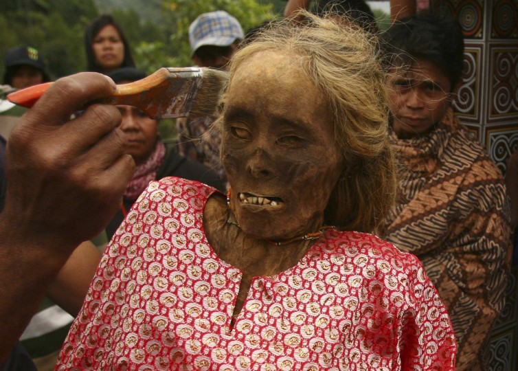 A family member cleans a mummy before giving it new clothes in a ritual in the Toraja district of Indonesia's South Sulawesi Province. (Yusuf Ahmad/Reuters)