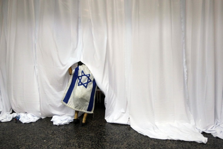 A boy covered in an Israeli flag lifts a curtain during a welcoming ceremony for Jewish immigrants from North America upon their arrival to Israel, at Ben Gurion International Airport near Tel Aviv. Israel's Prime Minister Benjamin Netanyahu welcomed the 350 immigrants at an official ceremony in the airport on Tuesday. Out of the 350 immigrants, 127 of them plan to join the Israeli Defense Force. (Baz Ratner/Reuters)