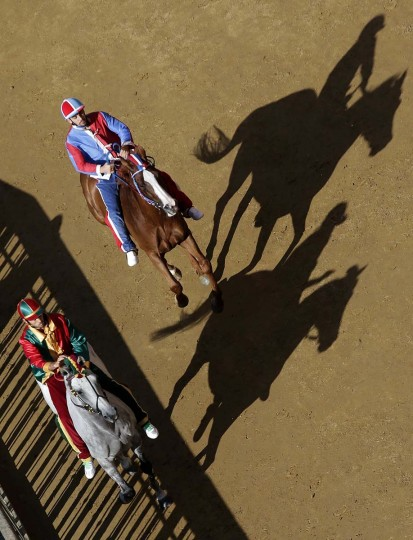 Jockey Antonio Siri (L) of the Drago parish rides his horse ahead of jockey Silvano Mulas of Pantera parish during a training session of the Palio race in Siena. Every year on August 16, almost without fail since the mid-1600s, 10 riders compete bareback around Siena's shell-shaped central square in a bid to win the Palio, a silk banner depicting the Madonna and child. (Alessandro Bianchi/Reuters photo)