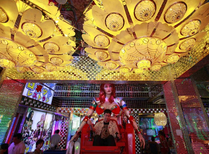 """A customer gives a thumbs-up as he is seated on a 3.6 meter-high custom-made female robot at the newly opened """"Robot Restaurant"""" in Kabukicho, one of Tokyo's best known red light districts, August 16, 2012. (Yuriko Nakao/Reuters)"""