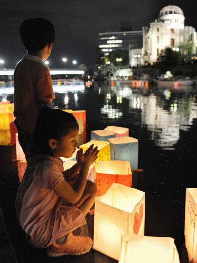 A girl prays after releasing a paper lantern on the Motoyasu river facing the gutted Atomic Bomb Dome in remembrance of atomic bomb victims on the 67th anniversary of the bombing of Hiroshima, in this photo taken by Kyodo August 6, 2012. (Kyodo/Reuters)