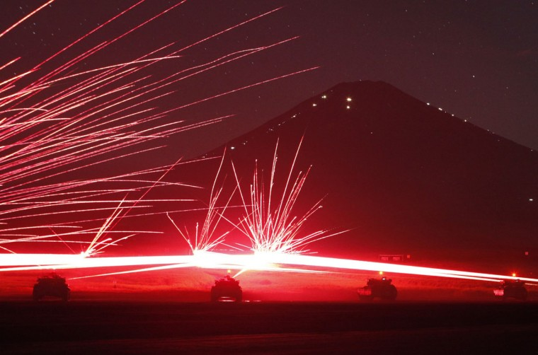 Tracer bullets ricochet off their targets as the Japanese Ground Self-Defence Force Type 74 and Type 90 armoured tanks fire machine guns during a night annual training session at Higashifuji training field in Gotemba, west of Tokyo. Mt. Fuji is seen in the background. (Issei Kato/Reuters)