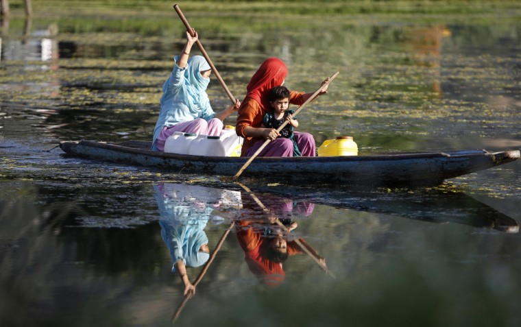 Kashmiri women row a boat in the waters of Dal Lake during the evening in Srinagar. (Danish Ismail/Reuters)
