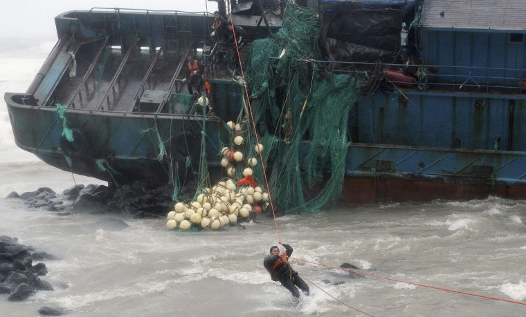 A Chinese fisherman gets out of a stranded Chinese fishing boat by using a rope while South Korean policemen rescue him and other fishermen in Seogwipo on Jeju Island, south of Seoul. A typhoon with winds of up to 170 kmh (106 mph) buffeted South Korea's west coast on Tuesday, killing five people at sea and leaving 10 missing when two Chinese fishing vessels capsized. (Gang Jae-Nam/Newsis/Reuters)