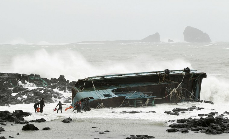 South Korean maritime policemen rescue a Chinese fisherman (4th L) from a stranded Chinese fishing boat in Seogwipo on Jeju Island, south of Seoul. Typhoon Bolaven barreled up the coast before making landfall in already flood-ravaged North Korea as the impoverished country struggles to feed its 24 million people. (Gang Jae-Nam/Newsis/Reuters)