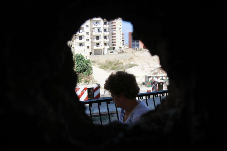 A woman is seen from a hole in her home's wall, caused by clashes between Sunni Muslims and Alawites in Tripoli, northern Lebanon August 27, 2012. (Omar Ibrahim/Reuters)