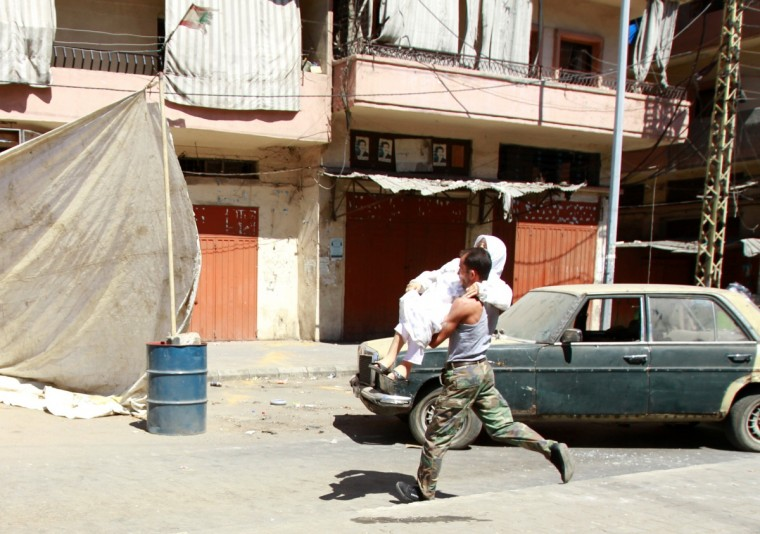 A Lebanese Sunni Muslim fighter carries a woman away from clashes at the Sunni Muslim dominant neighborhood of Bab al-Tebbaneh in Tripoli, northern Lebanon. (Omar Ibrahim/Reuters)