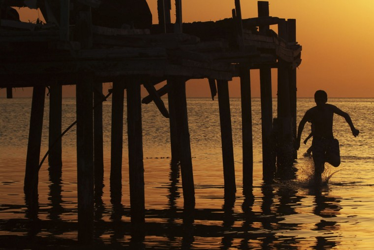 A boy runs in the water near a pier at sunset in Tripoli August 13, 2012. (Esam Al-Fetori/Reuters)