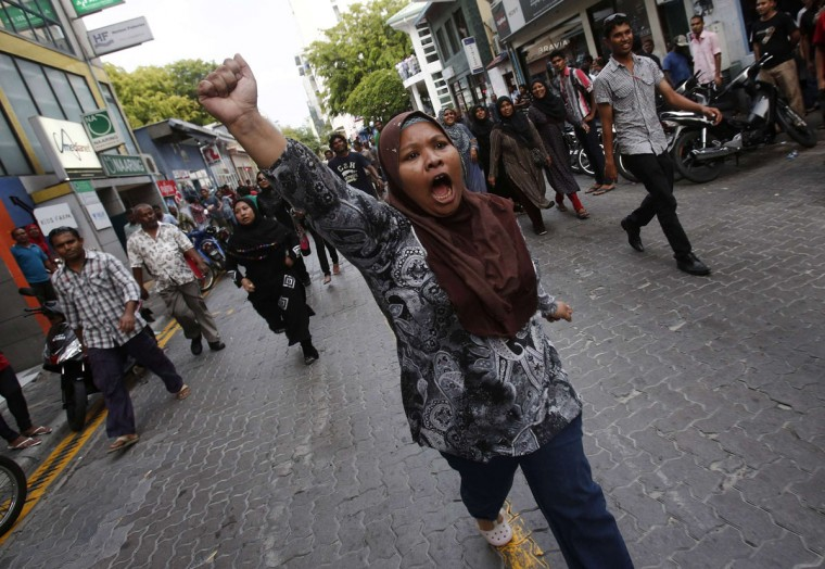A supporter of former Maldives' President Mohamed Nasheed runs as she shouts slogans during a protest in the capital, Male. About 1,000 supporters of the former president poured into the streets to denounce an internationally backed report which said the leader's removal earlier this year did not constitute a coup. (Adnan Abidi/Reuters)