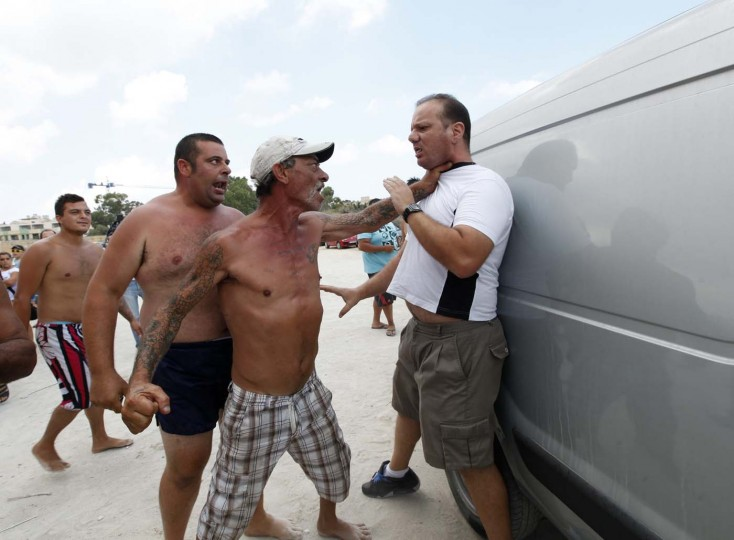 A camper grabs a man, who is taking part in a protest against camping on the beach in Marsaxlokk, south of Malta August 12, 2012. The man is part of a group of Marsaxlokk residents who are demonstrating against campers at the beach, who they say are taking up space and dumping rubbish inappropriately, according to local media. (Darrin Zammit Lupi/Reuters)