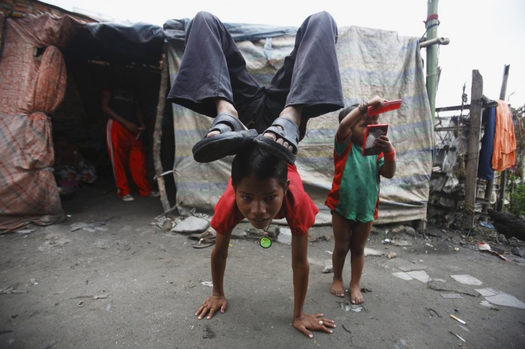 Drumpal Choudhary, 11, a street performer, does a hand stand in front of his hut in the slum on the bank of Manahara River before leaving to perform on the streets of Kathmandu. Drumpal and his siblings, Shivani and Gchan, who came to Kathmandu from India 5 years ago, earn their living by performing tricks on the streets of Kathmandu. According to Drumpal, Shivani's older brother, they earn around $10 a day by performing tricks, which is not enough to feed their 10-member family living together in a small hut without a proper toilet or any basic needs. (Navesh Chitrakar/Reuters)