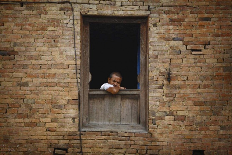 A man falls asleep while he sits at the window of his house in Lalitpur August 31, 2012. (Navesh Chitrakar/Reutrs photo)