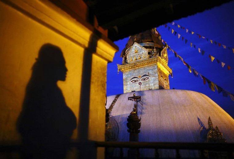 The shadow of a woman is cast on the wall of a monastery as she looks on toward the Swayambhunath Stupa in Kathmandu, Nepal. The Swayambhunath Stupa is a collection of shrines and temples. (Navesh Chitrakar/Reuters photo)
