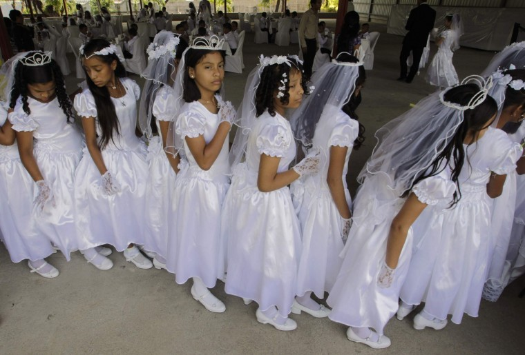 Children wait in line after receiving their first holy communion at Metropolitan cathedral in Managua. Around 150 children received their first holy communion during a mass organized by a local radio station. (Oswaldo Rivas/Reuters)
