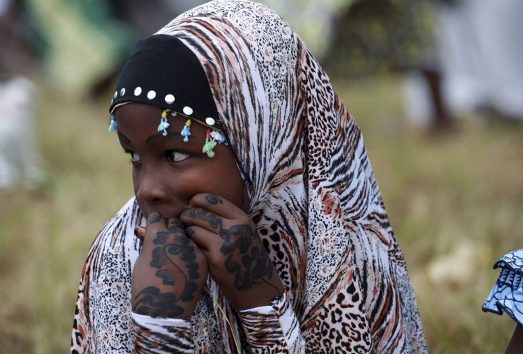 A girl sits in an open ground before the start of prayers for Eid al-Fitr celebrations, marking the end of the holy month of Ramadan in Nigeria's commercial capital Lagos August 19, 2012. (Akintunde Akinleye/Reuters)
