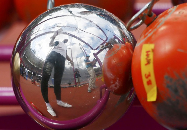 A competitor is reflected in a hammer during Group A of the men's hammer throw qualifications in the London 2012 Olympic Games at the Olympic Stadium. (Kai Pfaffenbach/Reuters)