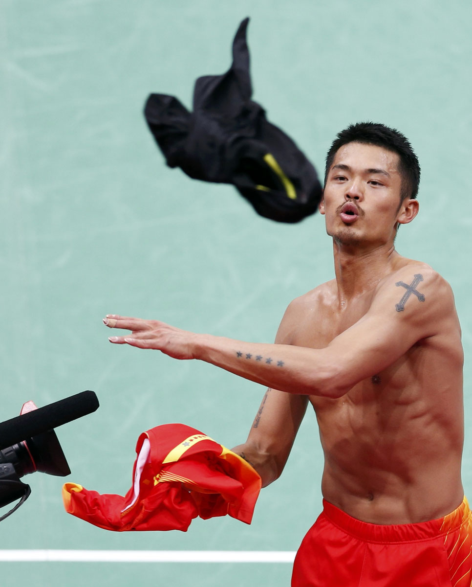 China's Lin Dan catches a T-shirt to change into after his win