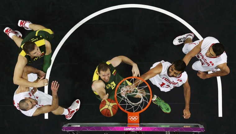 Lithuania's Renaldas Seibutis (C) tries to score against Tunisia's players during their men's preliminary round Group A basketball match at the Basketball Arena during the London 2012 Olympic Games August 6, 2012. (Sergio Perez/Reuters)
