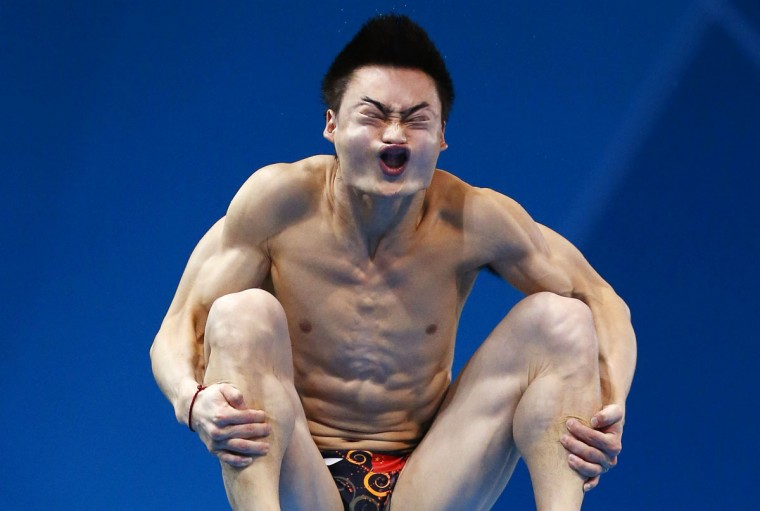 China's Qin Kai performs a dive during the men's 3m springboard preliminary round at the London 2012 Olympic Games at the Aquatics Centre. (Jorge Silva/Reuters)
