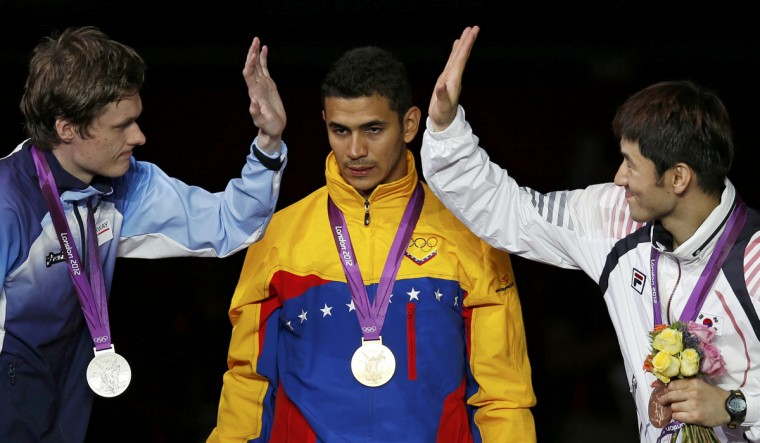 Norway's silver medallist Bastosz Piasecki (L) celebrates with South Korea's bronze medallist Jinsun Jung (R) near Venezuela's gold medallist Ruben Limardo Gascon during the men's epee individual fencing competition victory ceremony at the ExCel venue during the London 2012 Olympic Games. (Damir Sagolj/Reuters)